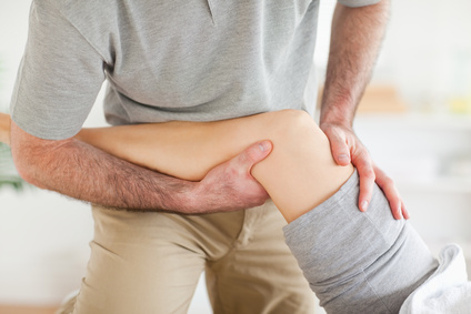 Chiropractor massaging a woman's knee